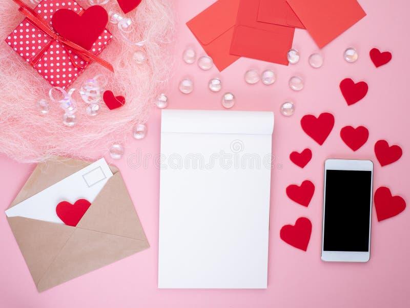 Подарок в красной подарочной коробке с смычком, блокнотом, умным телефоном, конвертом, c стоковое фото rf
