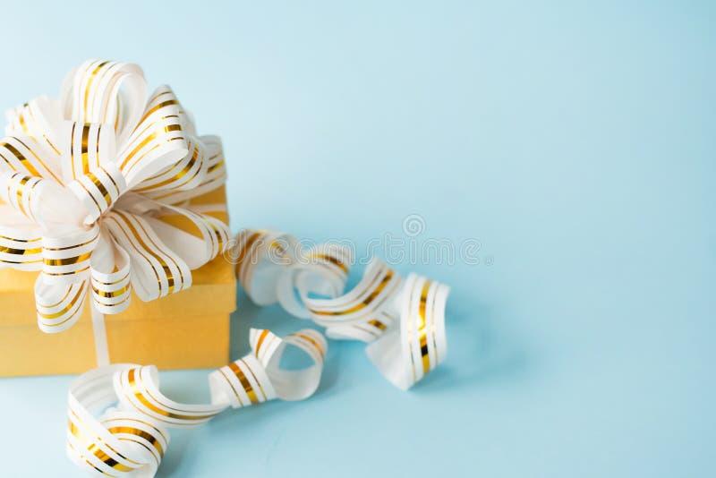Подарок в оболочке со смычком на голубой предпосылке с космосом экземпляра поздравительная открытка положенная квартирой стоковая фотография rf