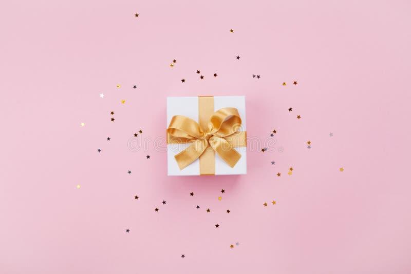 Подарок или присутствующий confetti коробки и звезд на розовом пастельном взгляде столешницы Плоский состав положения для дня рож стоковое фото rf