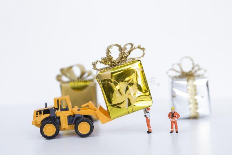 Подарок миниатюрного работника и желтой тележки moving стоковые фотографии rf