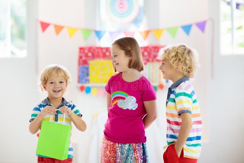 Подарок на день рождения ребенка раскрывая Ребенк на партии стоковая фотография