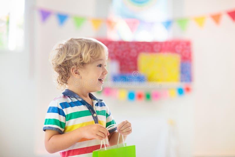 Подарок на день рождения ребенка раскрывая Ребенк на партии стоковые фото