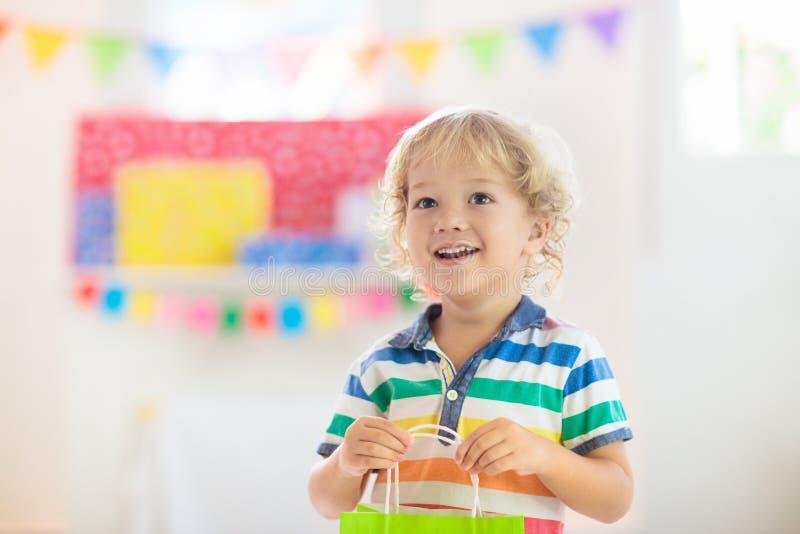 Подарок на день рождения ребенка раскрывая Ребенк на партии стоковое фото rf