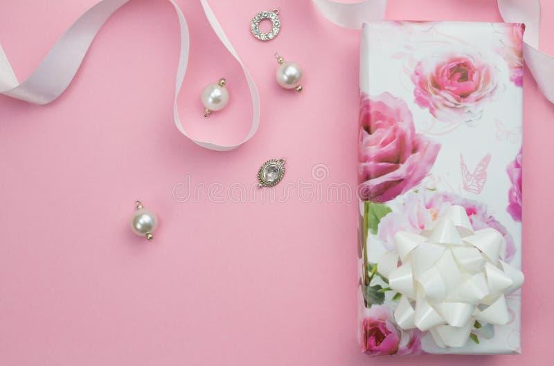 Подарок обернул коробку с лентой и шармы на розовой предпосылке с стоковая фотография rf