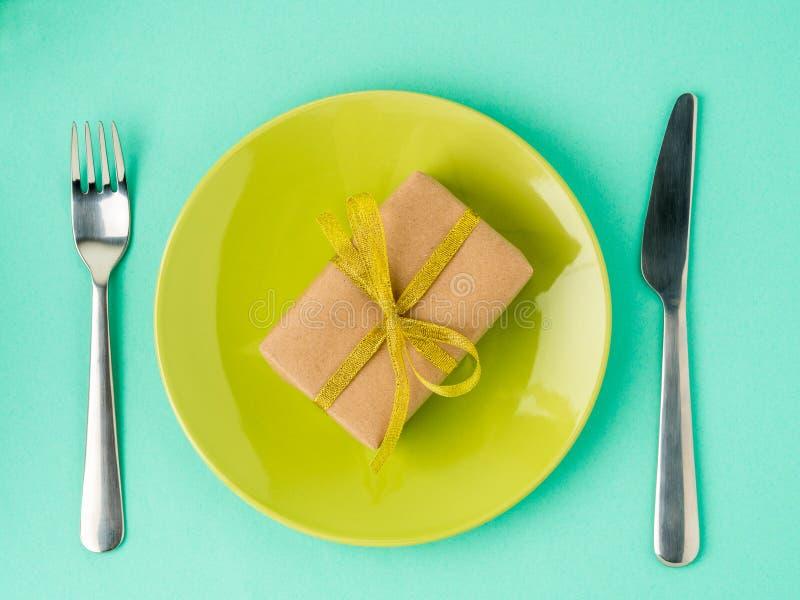 Подарок, пакет бумаги Kraft коричневой с золотой лентой на желтом pla стоковая фотография rf