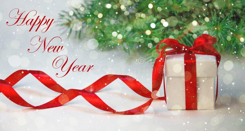 Подарок рождества в белой коробке с красной лентой на светлой предпосылке с елью Состав праздника Нового Года стоковое фото rf