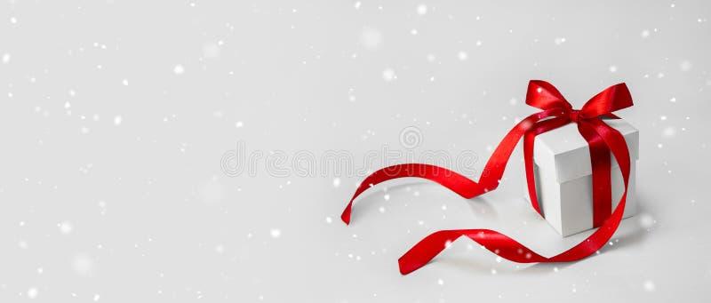 Подарок рождества в белой коробке с красной лентой на светлой предпосылке Минимальное знамя состава праздника Нового Года скопиру стоковые изображения