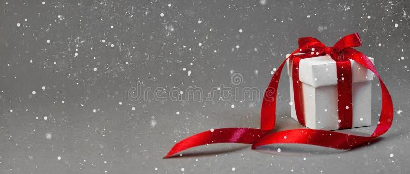 Подарок рождества в белой коробке с красной лентой на темной серой предпосылке Знамя состава праздника Нового Года скопируйте кос стоковое изображение rf