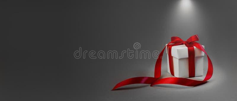 Подарок рождества в предпосылке красной ленты белой коробки темной серой Знамя состава праздника Нового Года фонарика концепции з стоковые изображения rf