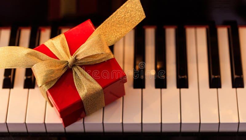 Подарок рождества на клавиатуре рояля, над взглядом стоковая фотография rf