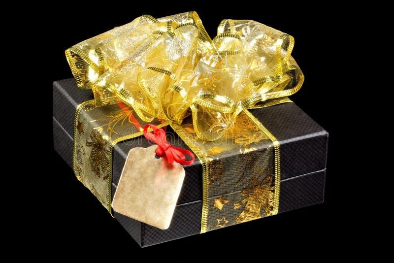 Подарок со смычком, лентой золота и ярлыком бирки на черной предпосылке с красным смычком Рамка ярлыка для указания важного текст стоковое фото