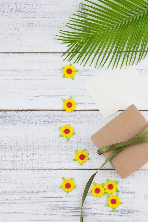 Подарочная коробка Брайна и пустая карточка украшают с листьями папоротника, желтыми бумажными цветками стоковая фотография rf