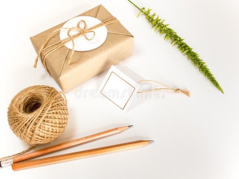 Подарочная коробка в оболочке в бумаге kraft и деревенской пеньке как естественный загородный стиль стоковое фото