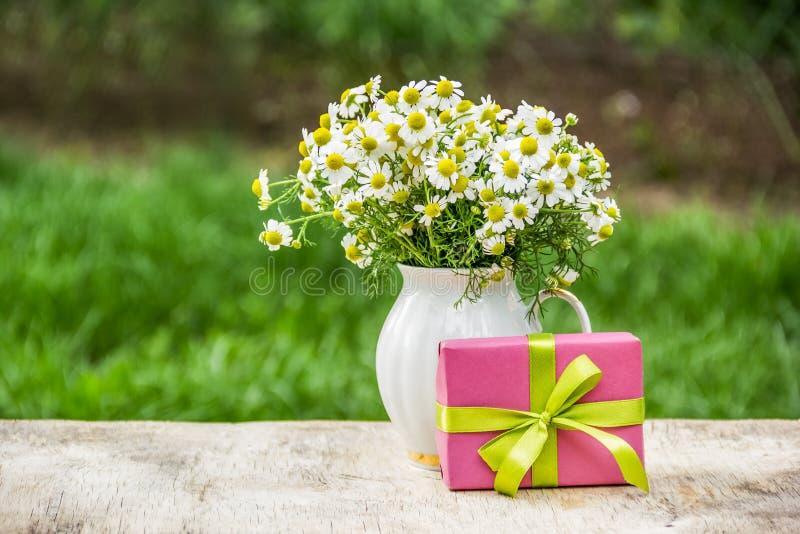 Подарочная коробка и букет цветков лета Стоцвет в вазе и подарке лето seashells песка рамки принципиальной схемы предпосылки стоковое фото