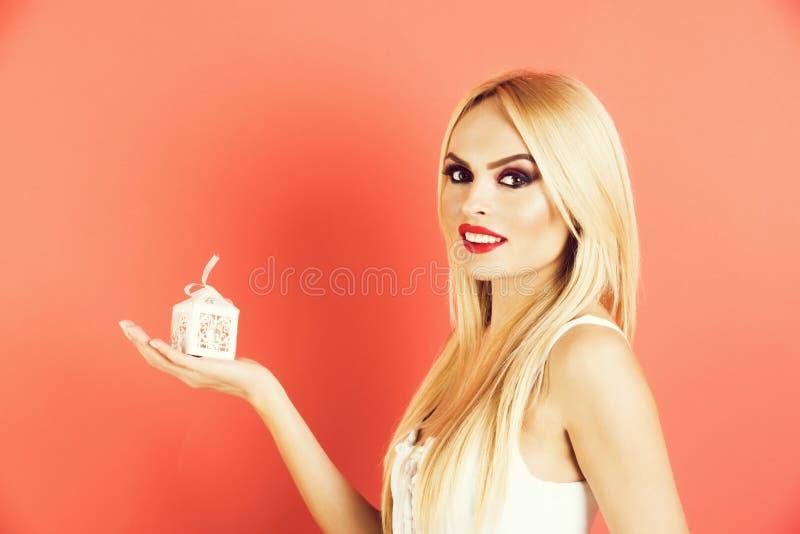 Подарочная коробка молодым обольстительным белокурым владением женщины малая белая стоковое фото rf