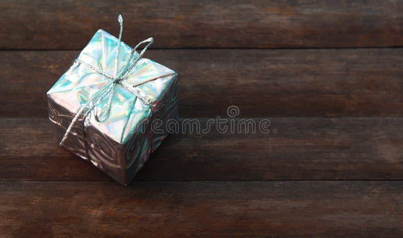 Подарочная коробка на деревянной предпосылке Настоящий момент в серебряной упаковочной бумаге с связанным смычком стоковая фотография rf