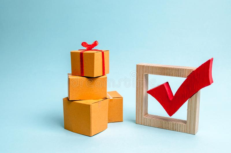 Подарочная коробка на куче коробок и красной контрольной пометки Концепция обнаружения идеального подарка Предложение списка поку стоковые изображения