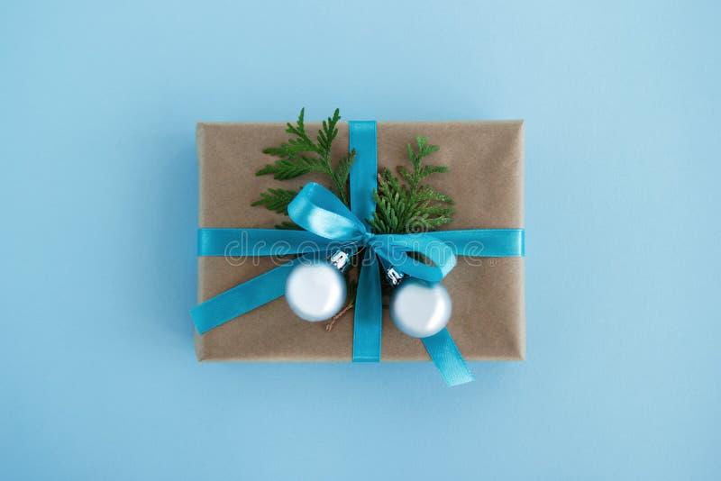 Подарочная коробка обернутая бумаги ремесла, голубой ленты и украшенных шариков ветви ели и серебряных рождества на голубой предп стоковые фотографии rf