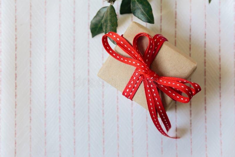 Подарочная коробка, обернутая в рециркулированной бумаге и красном смычке дальше на белом tabl стоковое фото rf