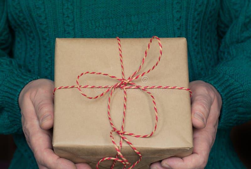 Подарочная коробка рождества владением руки ` s человека с красной лентой в зеленом свитере стоковые фото