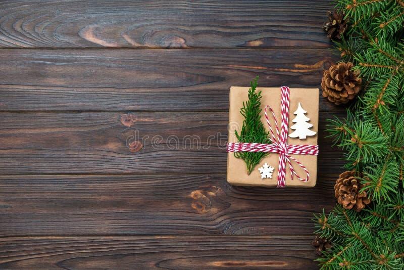 Подарочная коробка рождества в оболочке в повторно использованной бумаге, со смычком ленты, с лентой на деревенской предпосылке П стоковые фото