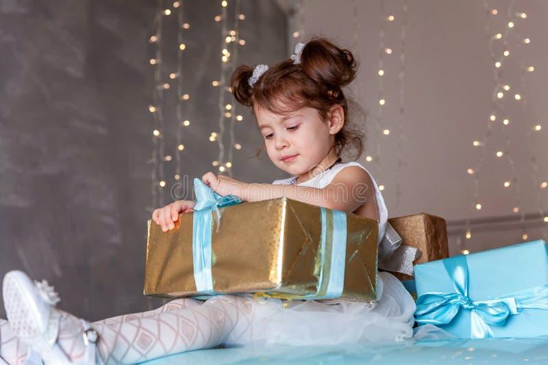 Подарочная коробка рождества маленькой девочки раскрывая стоковые фотографии rf