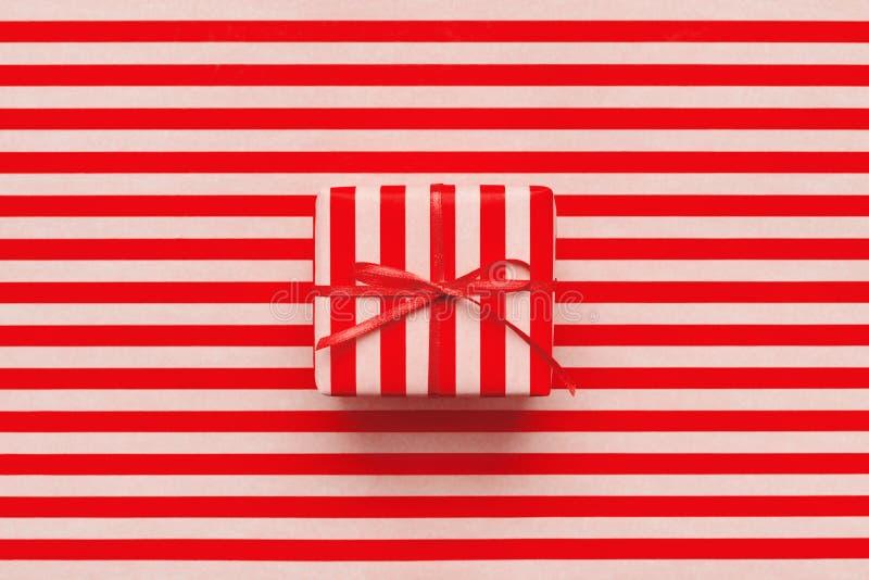 Подарочная коробка рождества на пинке и красной striped упаковочной бумаге стоковые фотографии rf