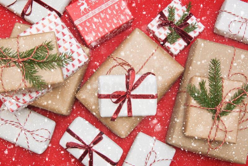Подарочная коробка рождества обернутая в бумаге орнамента и декоративной ленте красной веревочки на красной поверхности Творческо стоковые фотографии rf