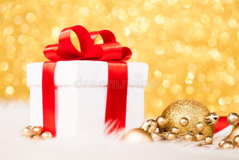 Подарочная коробка рождества против предпосылки bokeh золота стоковое изображение rf