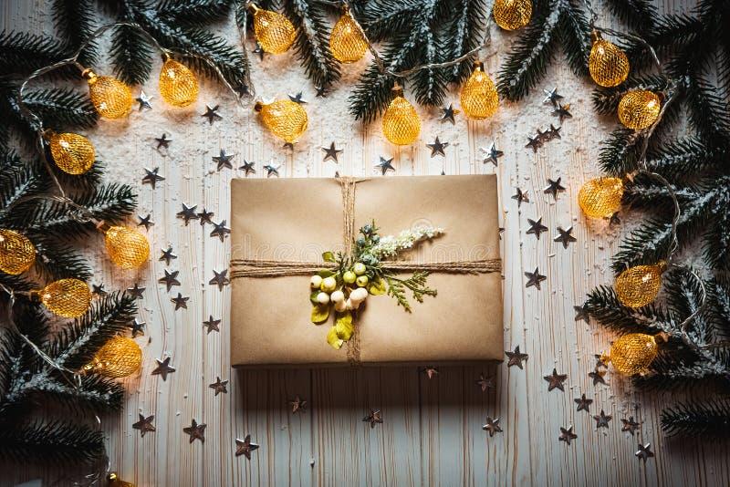 Подарочная коробка рождества с смычком и красивая накаляя гирлянда против белой деревянной предпосылки с ветвями стоковые фотографии rf
