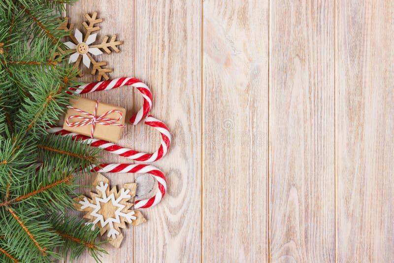 Подарочная коробка рождества, тросточка конфеты с снежинкой и ветвь ели на деревянном столе стоковая фотография