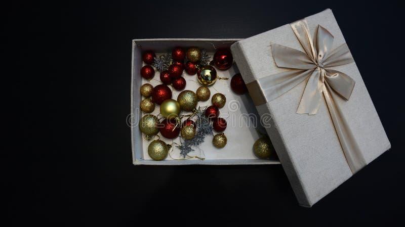 Подарочная коробка с глобусами рождества внутрь против темной предпосылки стоковые фотографии rf