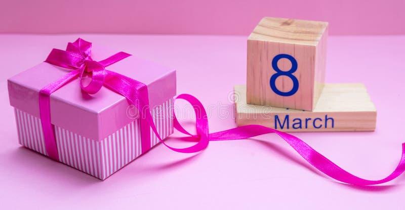 Подарочная коробка с лентой и день 8-ое марта женщин на розовой предпосылке стоковые фотографии rf