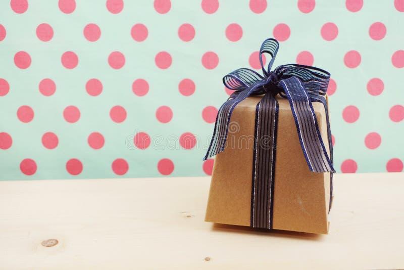Подарочная коробка с лентой смычка голубой ленты на деревянной предпосылке стоковое фото rf