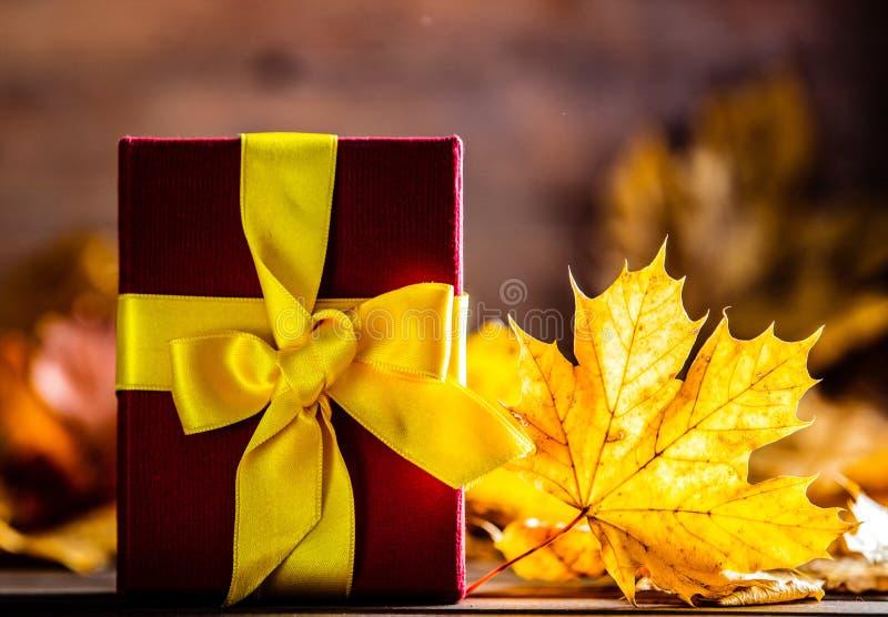 Подарочная коробка с смычком и кленовые листы на деревянном столе стоковые изображения