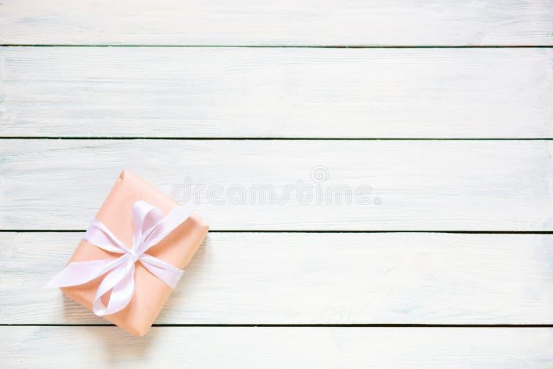 Подарочная коробка цвета персика на белой деревянной предпосылке r Свободное место для вашего положения текста плоского стоковая фотография rf