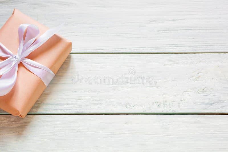 Подарочная коробка цвета персика на белой деревянной предпосылке r Свободное место для вашего положения текста плоского стоковые фото