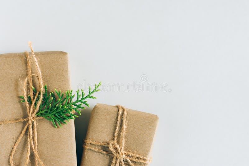 2 подарочной коробки обернутой в бумаге ремесла с хворостиной можжевельника на белой предпосылке Продажа настоящих моментов Новых стоковое фото