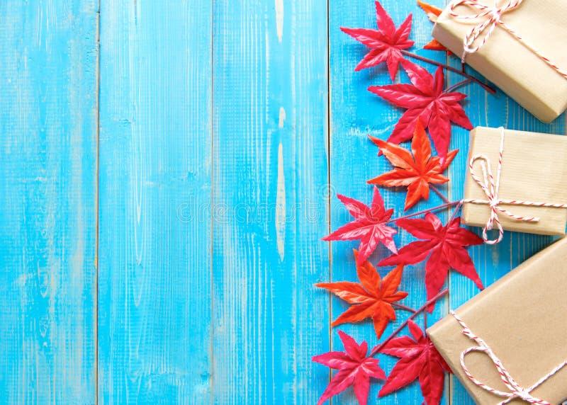 Подарочные коробки и клен рождества на голубой деревянной предпосылке стоковые изображения rf