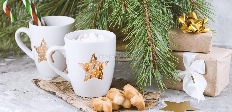 подарочные коробки, кружка с напитком украшенным с зефиром и печенья формы звезды около вечнозеленого бетона ветвей рождественско стоковое фото rf