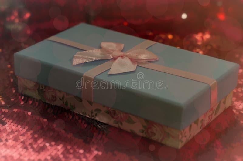 Подарочные коробки лежат на красной блестящей ткани Пакет подарков на Рождество боке, маленькое дерево, яркий праздничный фон Раз стоковое фото
