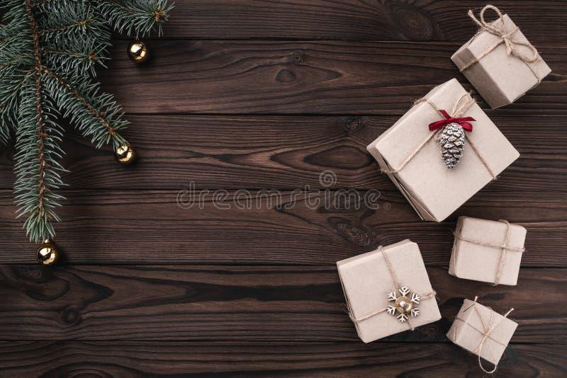 Подарочные коробки над темной деревянной предпосылкой Взгляд сверху Ель с безделушками, космос для текста стоковая фотография