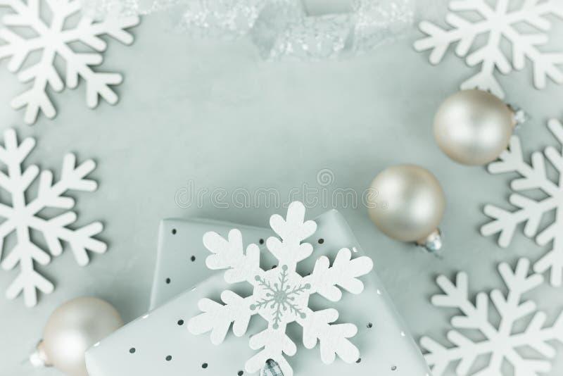 Подарочные коробки обернутые в серебряной бумаге Завитая серебряная лента Безделушки рождества, хлопья снега аранжировали в рамке стоковые фото