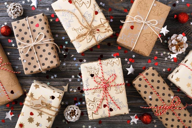 Подарочные коробки рождества & конусы сосны на украшенном праздничном острословии таблицы стоковое изображение