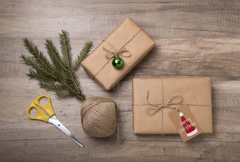 Подарочные коробки рождества обернутые в бумаге kraft, с пустой биркой подарка стоковые изображения rf