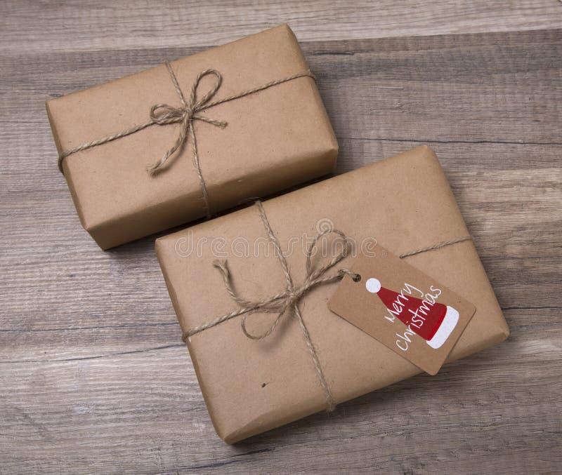 Подарочные коробки рождества обернутые в бумаге kraft, с пустой биркой подарка стоковое изображение