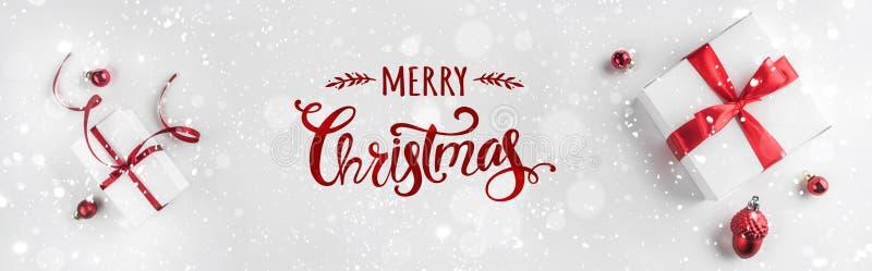 Подарочные коробки рождества с красными лентой и украшением на белой предпосылке Xmas и С Новым Годом! тема, снег стоковое фото