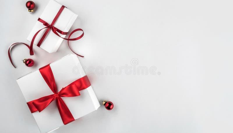 Подарочные коробки рождества с красными лентой и украшением на предпосылке белой бумаги Xmas и С Новым Годом! тема, bokeh стоковые изображения rf