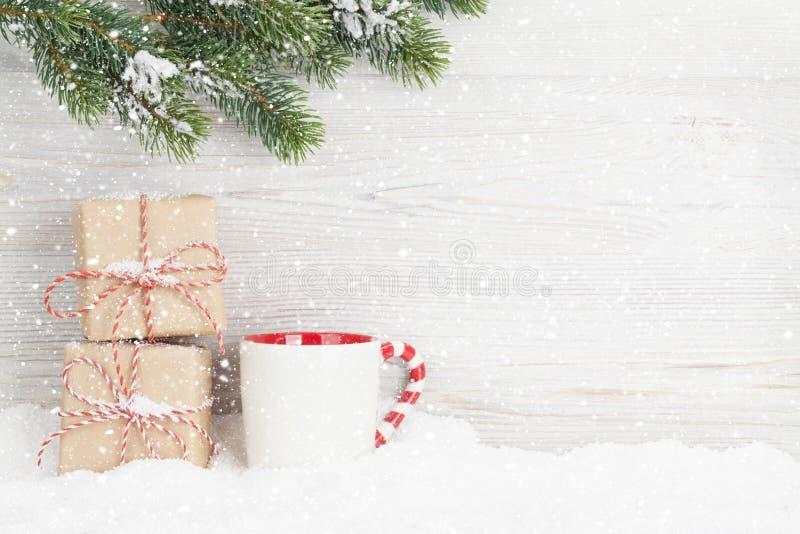 Подарочные коробки рождества, чашка горячего напитка и ель стоковое фото rf