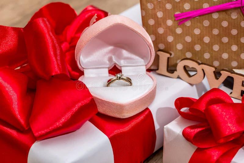 подарочные коробки с смычками ленты и открытая коробка с кольцом золота стоковое фото